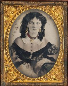 Hand-gilt tintype portrait of a young woman wearing a fine dress and jewellery, c.1868. Her dress is rather interesting - it looks as though the buttons up to the collar are on her bare skin, though obviously they can't be. [Via Southern Methodist Central University Libraries, DeGolyer Library, Lawrence T. Jones III Texas Photography Collection.]