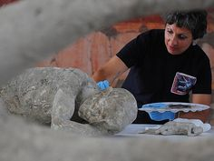 Cast in stone ... A restorer cleans and analyses the remains of one of 86 casts in Pompei