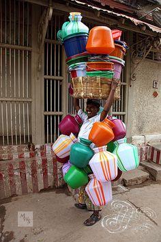 INDIA:  Kitchen pot salesman carrying his stock on his head, Madurai, Tamil Nadu