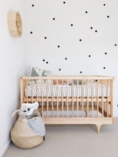 Beautiful modern and minimalist nursery, white and wood with polka dots wall…