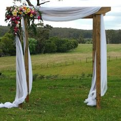 This timber wedding arch with draping white material looks fabulous on the farm. Dressed with bright coloured flowers. For more wedding arch inspiration and ideas you can visit us at .au for all you wedding hire. Diy Wedding Arbor, Wedding Trellis, Wedding Arch Rustic, Wedding Hire, Wedding Archways, Wedding Ceremony, Wedding Ideas, Wedding Stage, Wedding Draping