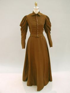 Brown wool day ensemble 1890 -1895 olive drab/ brown womans day-dress [wool]    Trim: There are twelve metal shank buttons with a flower design. The flowers were painted but most of the paint has faded or been worn away.