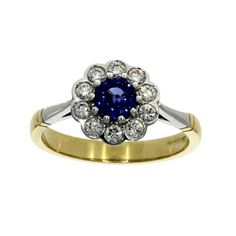 A sapphire and diamond cluster ring consisting of a principal sapphire in a 18ct white gold 10 claw setting surrounded by diamonds in 18ct white gold scallop settings with 18ct white gold shoulders and mounted on a plain 18ct yellow gold shank.