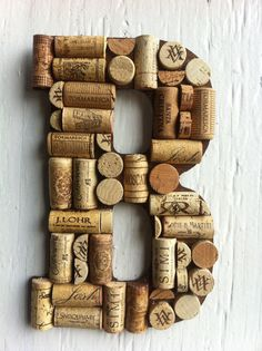 Handmade Letters and symbols made of Wine Corks. Purchase wooden letters, soak corks in hot water for 10 minutes before cutting to reduce crumbling, carefully weild a sharp Exacto knife, heat up a glue gun and get crafting!