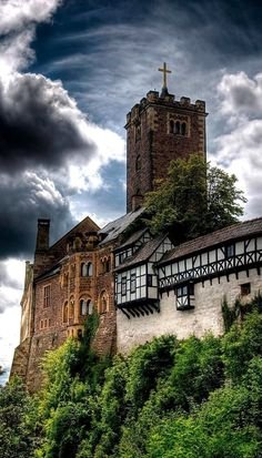 Wartburg Castle, Eisenach, Thuringia, Germany. The Wartburg is a castle originally built in the Middle Ages, situated on a 1,350 ft. precipice to the southwest of, and overlooking the town of Eisenach. It houses a museum focused on art from the Middle Ages. It is most famous for sheltering Martin Luther while he translated the New Testament into German. (V)