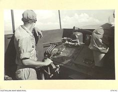 BOISA ISLAND, NEW GUINEA. 1944-06-19. THE SKIPPER AT THE CONTROLS OF AN UNITED STATES NAVY TORPEDO BOAT DURING A PATROL ALONG THE COAST. Mtb, Brown Water Navy, Pt Boat, East Indies, United States Navy, Power Boats, South Pacific, World War Ii, Wwii