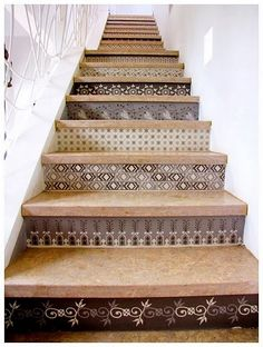 Wallpaper on the front of stairs. Different wallpaper in the same cool scheme on each step.