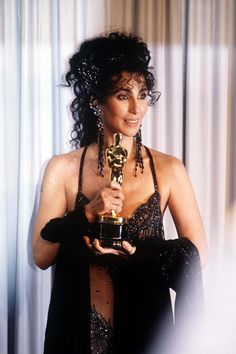 Cher clutching the Best Actress Oscar Paul Newman had just presented to her, backstage at the 60th Academy Awards ~ Cher had won for her performance in Moonstruck (1987)