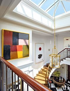 As part of their update of a New York City duplex, John B. Murray Architect and interior design firm Cullman & Kravis strikingly transformed the entrance hall, where an expanded skylight now illuminates paintings by (from left) Sean Scully, Adolph Gottlieb, and Giorgio Cavallon; the vintage Louis XVI–style lantern is from Newel, and the English Regency center table is from Niall Smith Antiques | archdigest.com