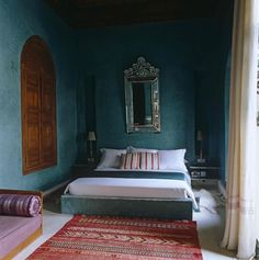 An attic bedroom decorated in blue and white. The room has exposed rafter beams and a painted wooden floor. The room is simply furnished with a double sleigh bed and a collection of glassware stands on a wood writing desk. Decor, Interior, Home Decor Bedroom, Home, Home Bedroom, Minimalist Bed, Woman Bedroom, Bedroom Carpet, Persian Decor
