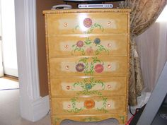 primer/sealer old dresser,2 satin colors of paint,gold metallic dry brush technique along edges,wood applique flowers, stencil leaves, add lots of colored glass knobs..paint applique flowers with craft acrilyic paints, add dec. molding..painting it colors to match w/floers, nail gun where you want them..varnish several coats