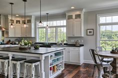 farmhouse kitchen remodel with black countertop white cabinets black top kitchen island with side open shelves and black white bar stools dark wood slabs floors of Tens of Inspiring Kitchen Islands with Storage and Chairs