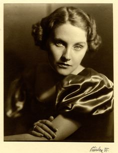 Black and white photograph of Nancy Spencer wearing a silky blouse, 1937