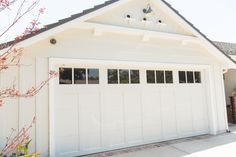 Clopay Coachman Collection steel and composite carriage house garage door in white. Design 12 with REC 13 windows. Photo Credit: Debra Morrison