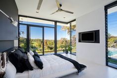 Floor-to-ceiling windows almost surround this modern black and white master bedroom and provide views of the backyard.