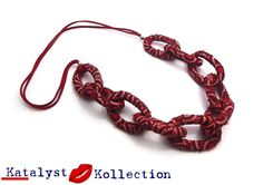 Handcrafted, Red Shweshwe drop, link necklace, wrapped with strips of Shweshwe African Print Fabric.The drop, link necklaceare lightweight and come in an assortment ofBlue, Green, Yellow and Red African fabric.Each colour of Shweshwe African Print Fabric accessories include: Small Stud Earrings