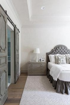 White and gray bedroom features a dark gray tufted arched headboard on queen bed dressed in white and gray bedding as well as a dark gray ruffled bedskirt placed next to a light gray cerused oak nightstand and a satin nickel tulip lamp placed atop a gray zebra rug.