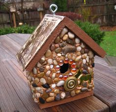 "Scottish Highlands Cedar birdhouse with stones and river rock collected from the shores of Lake Michigan, local rivers and from creek beds and recycled embellishments of metal Scottish Terrier dogs and art glass beads with a brass knob for perch. Roof and base is weatherproof stain in chocolate brown and roof has a embossed faux copper tile. Suitable for outdoor or indoor décor. Removable base for easy clean out.         1 1/4"" opening   $56.00 plus shipping"