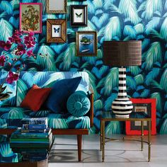 Matthew Williamson in collaboration with Osborne & Little. The Tropicana wallpaper and fabric from the 2015 Cubana collection. A stylised palm leaves on a contrasting ground. A couch and wallpaper are shown in the same print.