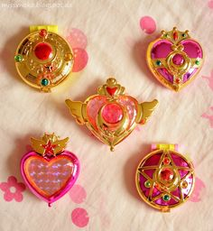 All Sailor Moon Compacts ♥ • Crisis Moon Compact クライシス・ムーン・コンパクト (middle) • Cosmic Heart Compact コズミック・ハート・コンパクト (top left) • Crystal Star クリスタル・スター (bottom left) • Transformation Brooch 変身・ブローチ / Sailor Locket (top right) • Chibi Moon Compact ちびムーン・コンパクト (bottom right)
