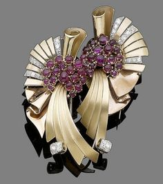 A ruby and diamond double-clip brooch, circa 1940. Of scrolling design, accented with circular cabochon rubies and old brilliant-cut diamonds