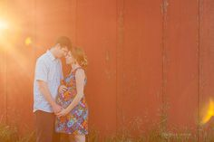 Pregnant couple behind barn, sunset maternity photo with sun flare  www.michellejackson.ca    A Summer Sunset Maternity Session-Edmonton Maternity Photographer