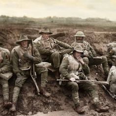 Unidentified men of the Australian 5th Division enjoying a smoke and rest by the side of the Montauban road, near Mametz, France, while en-route to the trenches. Most of the men are wearing sheepskin vests and woollen gloves, and are carrying full kit and .303 Lee Enfield rifles, December 1916. [Colorized by Benjamin Thomas]