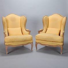 Pair High Back Winged Bergeres With Matching Stools  --  Pair circa 1920s down filled wing chairs found in France with coordinating ottomans. Details include carved wood frames, padded arms and decorative brass nail heads. Yellow fabric upholstery shows some wear and discoloration.  Structurally, the chairs, stools and down cushion inserts are in excellent condition. Sold and priced as a pair.  --   Item:  6784  --  Retail Price:   $7095