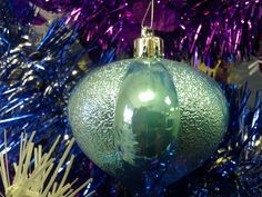 Light Blue ornament surrounded by purple, silver, white, and blue