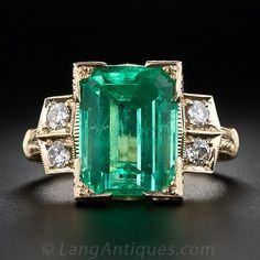 An extra-bright and lively green emerald, weighing 6.26 carats, is presented in timeless vintage fashion in this newly made, antique style ring, expertly hand crafted and lavishly hand engraved in rich 18 karat yellow gold with four small sparkling accent diamonds. The rare and wonderful crystal-clear emerald is set with four geometric prongs and adorned on two sides with a decoratively pierced gallery. The beveled diamond-set shoulders gracefully transition down to an elegantly sculpted and…