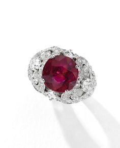 Superb 'Pigeon Blood' Ruby and Diamond Ring, Cartier. Set with an 8.37 carat cushion-shaped Burmese ruby, within a mount of scroll design set with pear-shaped, step- and brilliant-cut diamonds.