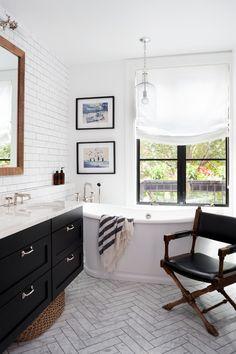 Bathroom with herringbone floor tile, white subway tile wall, free standing tub, black vanity with marble countertop | BGDB Interior Design