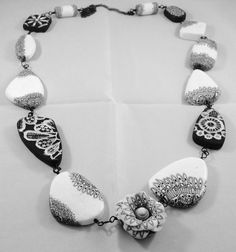 By Debby Wakley Black and white necklace, using fimo professional polymer clay. Random beads textured with lace, using a lace cane.
