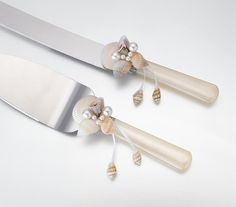 Ivory Seashell Wedding Cake Server Set features handles made of ivory acrylic. The top of each handle is decorated with a cluster of seashells with orange and tan color accents. This cluster also has faux ivory pearl decorations. Hanging from the seashell cluster are ivory satin ribbons with tiny a tiny seashell on the end. The blades are made of stainless steel.
