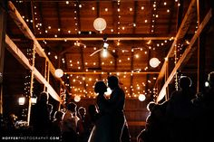 Fairy lights strung throughout the rafters add a romantic ambiance to this rustic reception | Hoffer Photography