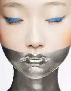 Photographer Pascal Demeester captures this futuristic conceptual beauty look. The silver makeup extending from the lips to the decolletage looks like a metal plate which contrasts nicely with the classic winged eyeliner.