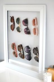 A Cute way to organize glasses and sun  glasses with a picture frame and some string, ribbon, or floral wire.