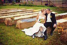 several good ideas in this photo - photo idea, hay bale seating, sunflower decor along aisles