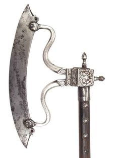 A seldom encountered form of Udaipur workmanship. The long, lightly-curved blade terminating in bird's heads, each with garnet eyes, retained by a pair of sinuous arms which spring from the chiseled socket. They are heavily embellished with inlaid silver panels in flower and vine motifs and terminating in a pair of lotus-bud finials.