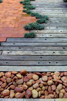 Piso externo de cruzetas, tijolo, pedra e grama preta.