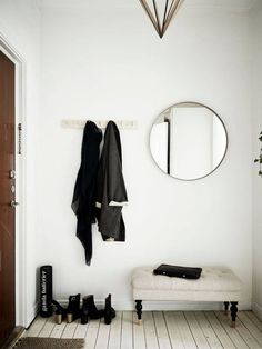 Simple white entryway with a round mirror, some coat hooks, white floorboards and a small bench.