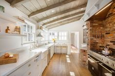 Cottage kitchen features sloped, planked ceiling accented with wood beams and pot lighting