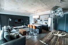 salon gris moderne aménagé avec un canapé gris, une table basse style industriel en bois massif et plafond béton exposé