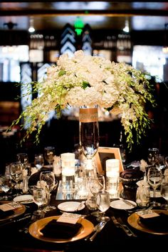 Lush White Floral Centerpiece, on a mirrored glass. Gold platters set off with a black table cloth and serviettes, crystal glasses and silver cultery. Looks wonderful for a New Years Eve Party or a special event in your life - not a wedding. JH