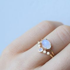 -solid 14kt gold -natural 3mm rainbow moonstone -natural 2mm white sapphires A simple pastel colored arc ring, made up of a divine combination of rainbow-moonstone and sapphire. Looks great paired wit
