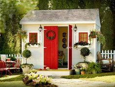 A mini white picket fence, window planter boxes and a red door, it doesn't get much cuter.