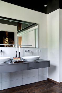 Das natürliche Bad-Design wird gekonnt durch moderne Elemente wie die Aufsatzbecken am Waschtisch akzentuiert