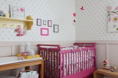 beautiful pink crib and wallpaper in this small nursery