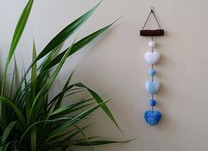 """Amazing pompon wall hanging with handmade acrylic pompons hanging by a metal chain. Length 20,47 (52 cm). Width of wooden stick (oak) 4,33 (11 cm). The wood has been hand sanded and finished with an oil finish. Diameter of pompons 1,18 (3 cm). Sizes of pompom hearts 2,76 x 2,36"""","""