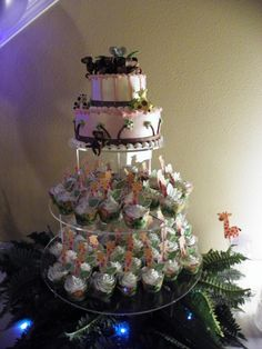 Safari Baby Shower Cake accented with cute fondant zebra, giraffe, monkey and elephant. surrounded with safari cupcakes
